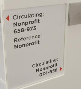 Nonprofit Resource Center shelves with directional signs pointing to reference and circulating nonprofit items.