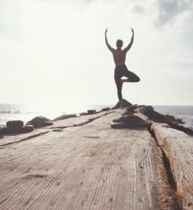 man standing while raising his hands at seashore